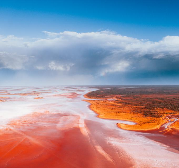 A pink and shimmering salt lake with blue sky and clouds